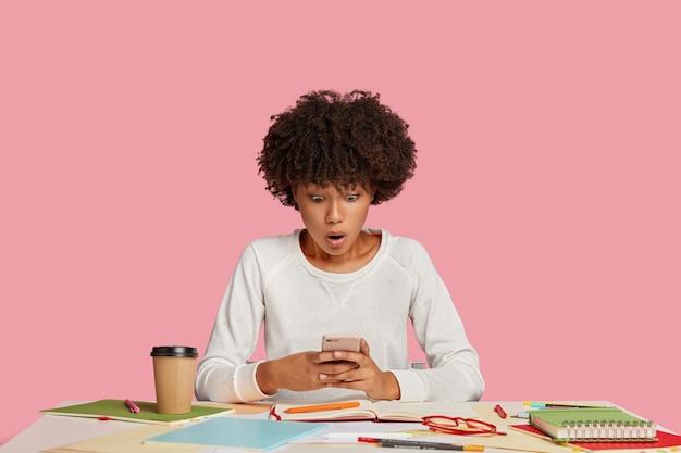 Inquadratura orizzontale del giovane freelance dalla pelle scura sorpreso pone circondato da quaderni e penne, scioccato nel leggere il messaggio di reddito sul cellulare