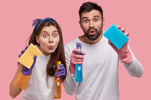 Horizontal shot of surprised handsome young guy and attractive woman holds sponges in front, carry detergents, clean windows at kitchen