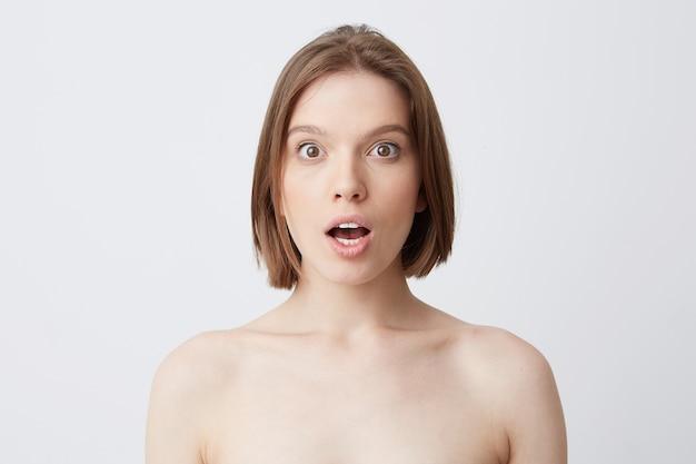 Colpo orizzontale di donna abbastanza giovane sorpresa con pelle morbida e sana dopo aver applicato la maschera