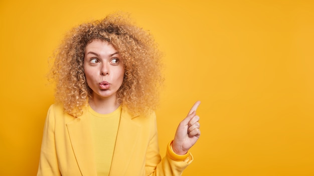 Horizontal shot of surprised wondered woman with folded lips suggests to look away shows blank space for your advertisement dressed in formal clothes isolated over yellow wall. look there
