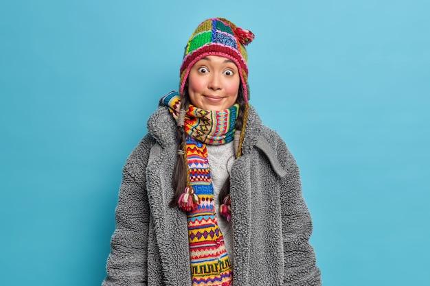 Colpo orizzontale di giovane donna asiatica sorpresa con guance rosee indossa sciarpa cappello lavorato a maglia intorno al collo e abiti caldi cappotto di pelliccia per il freddo isolato sopra la parete blu