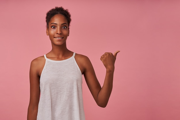 Colpo orizzontale di giovane donna dai capelli castani ricciuta attraente sorpresa che sfoglia da parte mentre levandosi in piedi sopra il muro rosa in camicetta bianca estiva