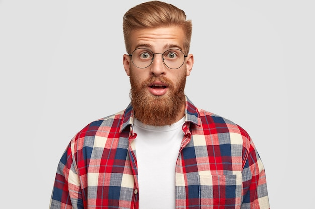 Horizontal shot of surprised young businessman has shocked expression, opens eyes widely, can`t beleive in failure, has thick ginger beard, wears checkered shirt, isolated over white wall