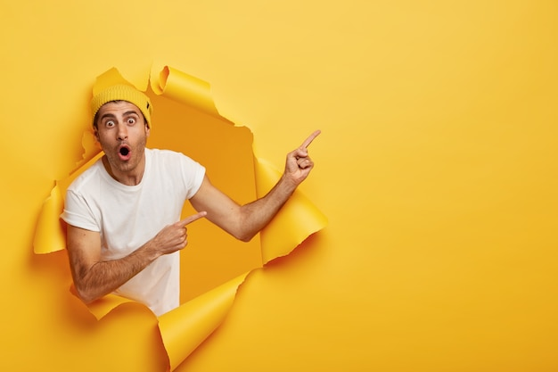 Horizontal shot of surprised young caucasian man in white t shirt and yellow headgear, has widely opened mouth