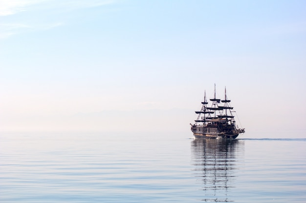 Horizontal shot of a tall ship sailing on beautiful clear water during daylight