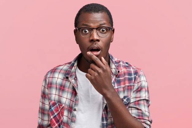 Horizontal shot of terrified male with shocked expression, keeps mouth opened and looks in bewilderment, wears glasses and casual t shirt, isolated over pink