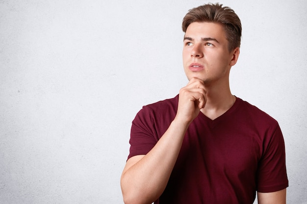 Horizontal shot of thoughtful male with appealing appearance and strong healthy body