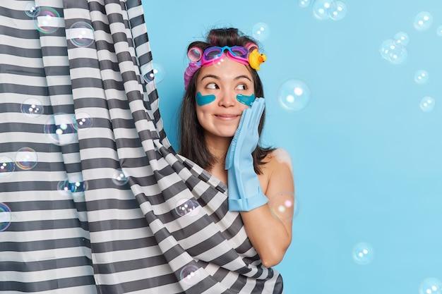 Il colpo orizzontale della giovane donna asiatica premurosa applica i bigodini tiene la mano sulla guancia applica i cuscinetti di bellezza sotto gli occhi i rulli dei capelli posa dietro la tenda della doccia prende la doccia si prepara per la data
