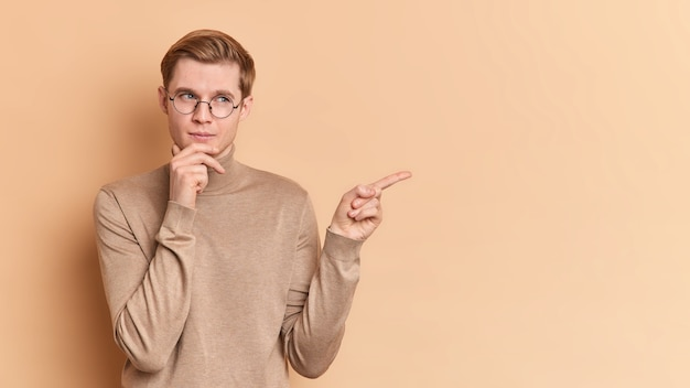 Horizontal shot of thoughtful young man holds chin thinks about suggested offer points away shows copy space for your advertising content wears round spectacles casual jumper