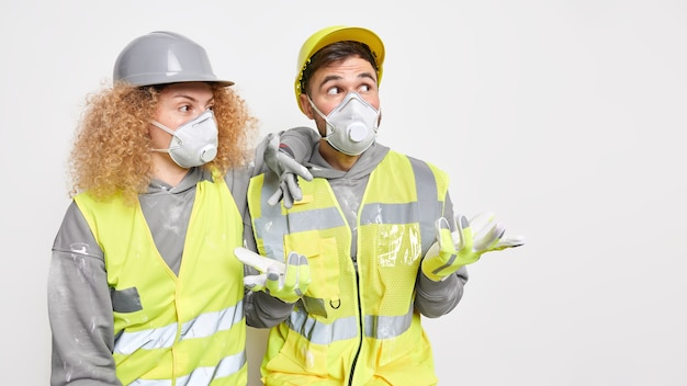 Horizontal shot of of two construction workers wear helmet protective masks and uniform