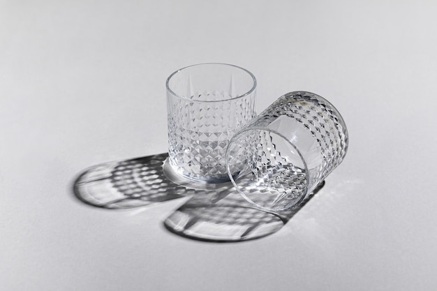 Horizontal shot of two empty old-fashioned glasses on the white surface with shadows