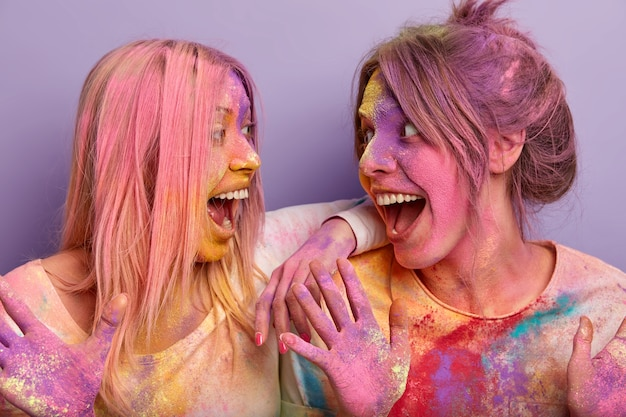 Horizontal shot of two happy women with colored hair, body and clothes, celebrate holi color festival, look happily at each other