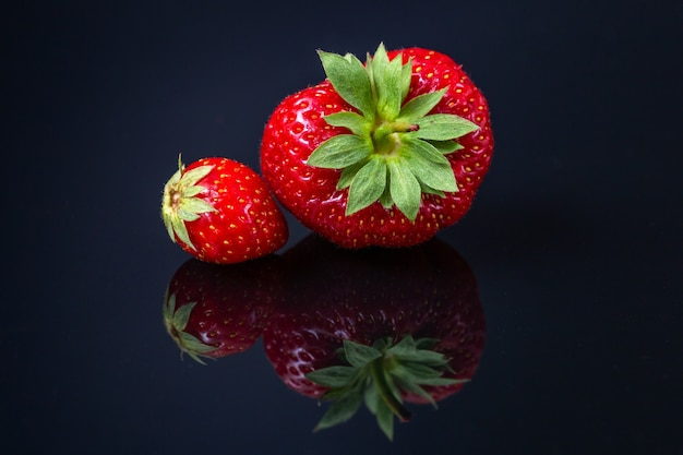 Horizontal shot of two red croatian strawberries on a black reflecting surface