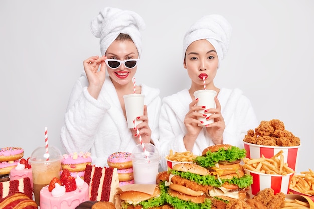 Horizontal shot of two women drink fizzy drink with straws wear domestic comfortable dressing gown