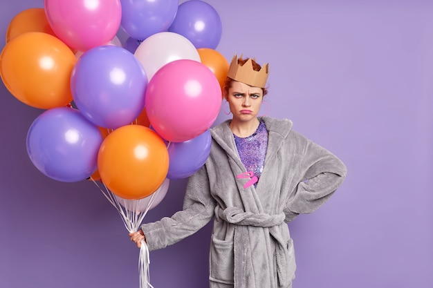 Horizontal shot of unhappy woman dressed in soft dressing gown and paper crown holds bunch of colorful balloons frowns face isolated over purple wall