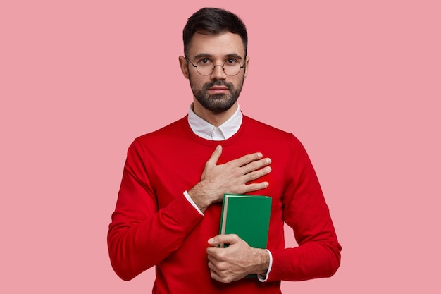 Horizontal shot of unshaven serious masculine college student promises to study hard, holds green textbook, wears red elegant sweater