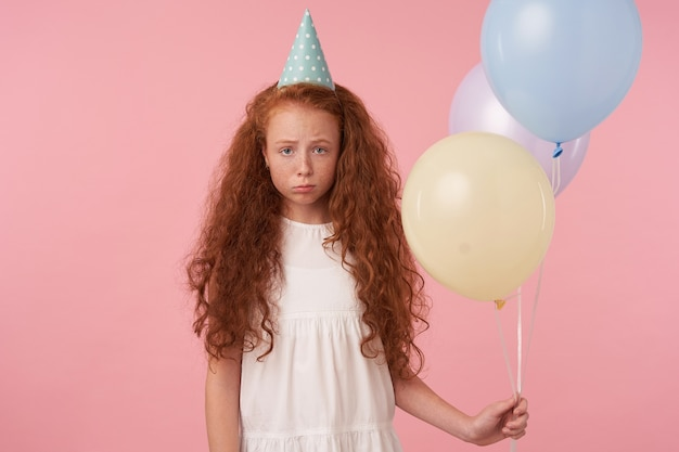 Horizontal shot of upset redhead little girl with long curly hair wearing festive clothes and birthday cap, looking at camera sadly and pursing lips, isolated over pink background with air balloons