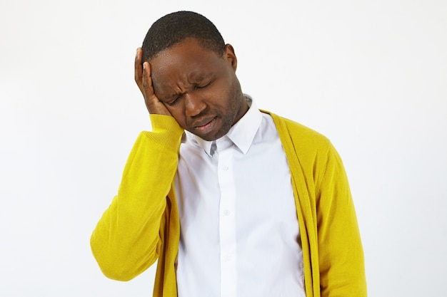 Horizontal shot of upset young dark skinned man having frustrated painful expression, closing eyes and holding hand on his head, suffering from terrible headache because of financial problems
