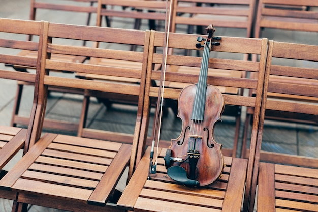 Horizontal shot of violin on wooden chair with bow. musical instruments concept.