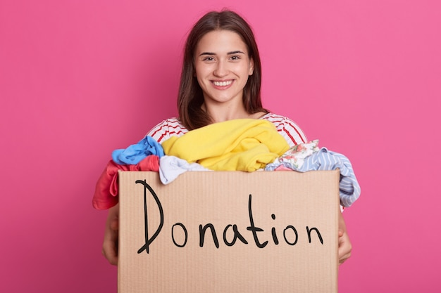 Horizontal shot of volunteer female standing isolated over pink, holding box with inscription donation, clothes for children`s home. smiling brunette woman making charity.