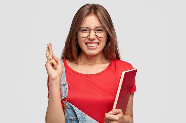 Il colpo orizzontale della donna caucasica desiderosa incrocia le dita, vestita in abiti casual, tiene il libro di testo rosso, stringe i denti, indossa occhiali rotondi, isolato sopra il muro bianco studenti e desiderio