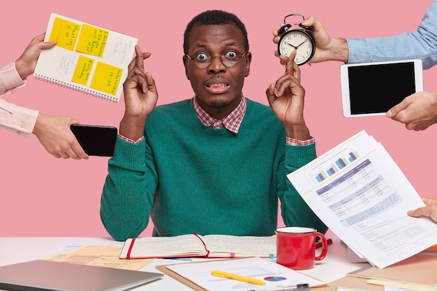 Horizontal shot of wishful dark skinned man crosses fingers, makes wish, dressed in green sweater, prepares for examination session, surrounded with alarm clock, touchpad