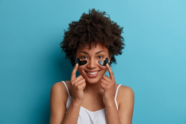 Horizontal shot of young afro american woman cares about skin, points at hydrogel anti aging moisturizer patches under eyes, enjoys beauty treatment, has broad smile, isolated on blue wall