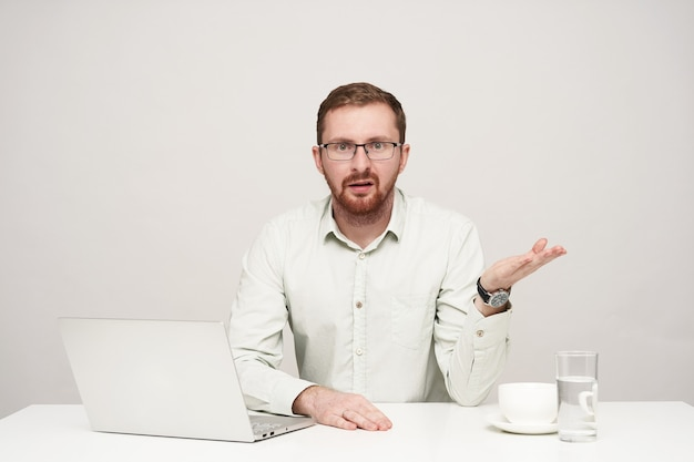 Horizontal shot of young bearded businessman in glasses raising perplexedly hand while looking confusedly at camera, being isolated over white background