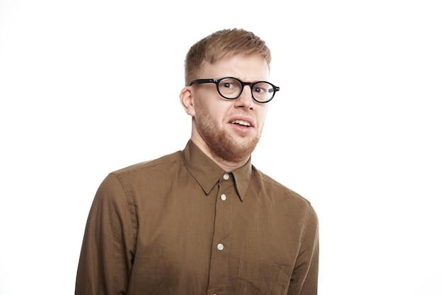 Horizontal shot of young bearded male of european appearance wearing eyeglasses and shirt having disgusted displeased expression, staring with disgust. human emotions and reaction
