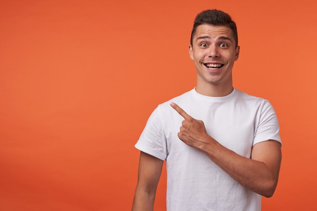 Horizontal shot of young brown-eyed short haired guy showing aside with index finger while looking joyfully at camera, standing over orange background