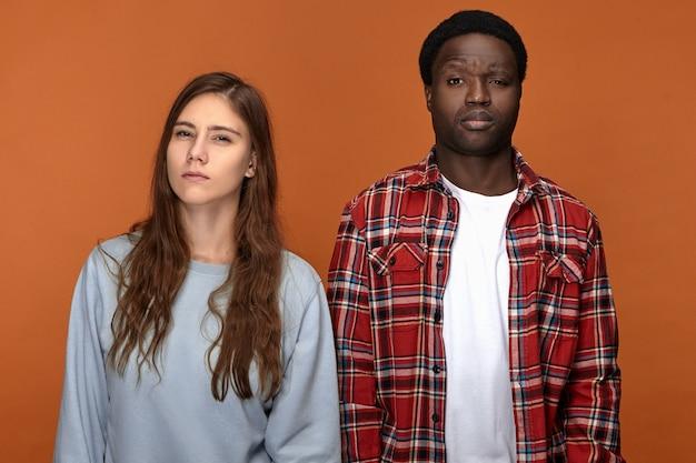 Colpo orizzontale di giovane femmina caucasica e maschio afroamericano in piedi uno accanto all'altro in, restringendo gli occhi, con espressioni facciali sospette. emozioni e reazione