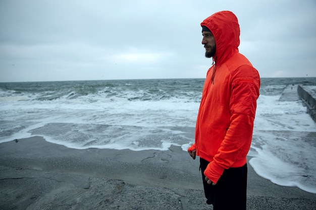 Horizontal shot of young dark haired bearded sportsman dressed in warm orange hoodie and black athletic trousers standing over seaside on grey early morning and looking thoughtfully ahead