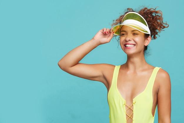 Inquadratura orizzontale della giovane femmina riccia felice alzando la mano alla testa e sorridente ampiamente pur avendo un bel tempo con gli amici sulla spiaggia, isolato su sfondo blu