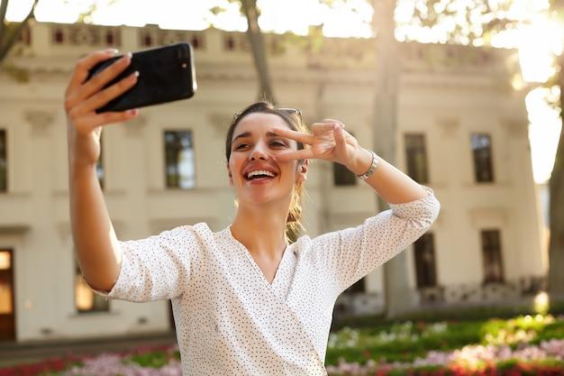 Inquadratura orizzontale della giovane bella signora bruna in abiti bianchi a pois facendo selfie con lo smartphone, alzando il gesto di vittoria sul viso e sorridendo ampiamente