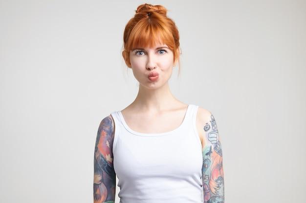 Inquadratura orizzontale della giovane bella donna tatuata con acconciatura bun imbronciato le labbra mentre scherza, vestito con un abbigliamento casual mentre posa su sfondo bianco