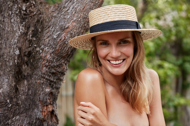 Horizontal shot of young lovely woman with pleased expression, wears straw summer hat, demonstrates perfect slim body, has vacations on exotic island