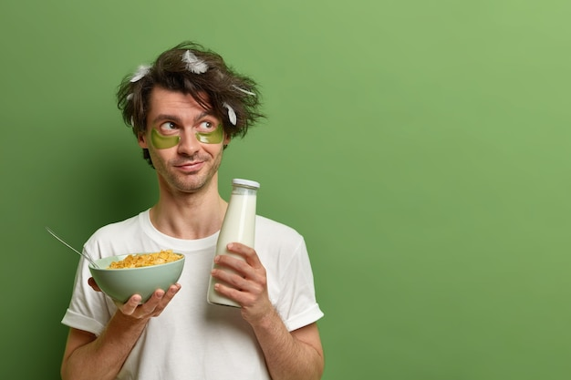 Horizontal shot of young man awakes in morning, holds bowl of cereals and milk for breakfast, has healthy nutrition or eating, keeps to diet, wears collagen patches, isolated on green wall.