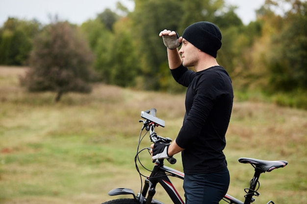 Horizontal shot of young man standing with bicycle in field and looking into distance, keeps hand near forehead, trying to see right way, handsome male wearing black sportwear.