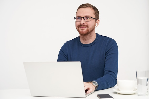 Horizontal shot of young pleased bearded fair-haired man looking positively ahead with lovely smile while keeping hands on keyboard, posing over white background