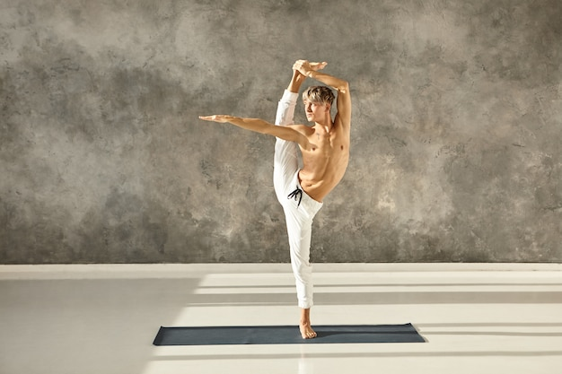 Horizontal shot of young professional man yogi posing shirtless indoors, doing vertical stand split on mat. handsome european blonde guy in white pants stretching legs muscles at gym during yoga class