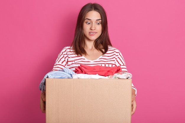 Horizontal shot of young volunteer stands with carton box full of donated clothes, adorable woman looking at clothes with scared facial expression, bits her low lip, lady wearing striped casual shirt.