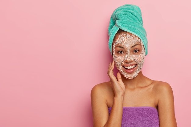 Horizontal shot of young woman cares about her skin, touches cheek with hand, takes shower and applies sea salt mask