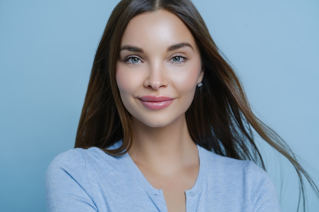 Horizontal shot of young woman with straight dark hair, fresh look and makeup, cares about her skin satisfied with skin care product leaves positive comment poses