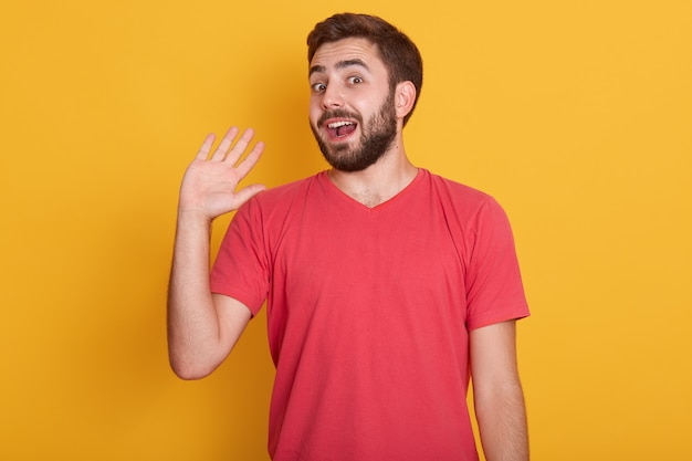 Horizontal shotof excited young man dresses red casual t shirt