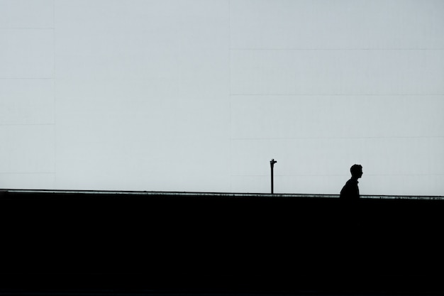 Horizontal silhouette of a lonely male under the clear sky