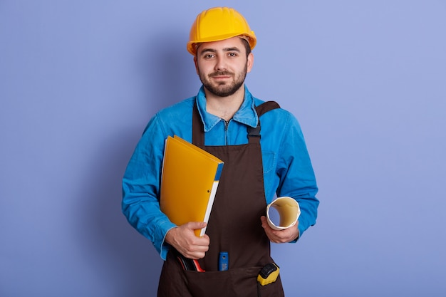 Horizontal studio picture of young handsome builder wearing blue uniform