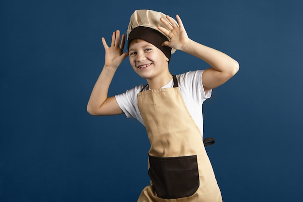 Horizontal studio shot of funny cute little boy dressed in beige chef hat and apron laughing, holding hands at his head, making faces, teasing someone. male child having fun. cooking and food concept