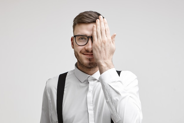 Horizontal studio shot of happy attractive young bearded businessman wearing formal clothes and glasses covering one half of his face while having his eyes examined at ophthalmology appointment