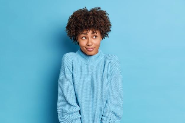 肌の色が濃い女性の横向きのスタジオショットは、楽しい何かについて考えています。素敵な夢があります。ニットのセーターを着た彼女の最初のデートを思い出します。