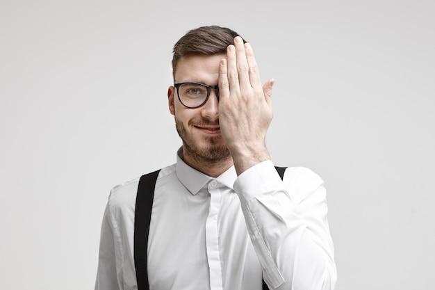 眼科の予約時に目を検査しながら、顔の半分を覆うフォーマルな服と眼鏡を身に着けている幸せな魅力的な若いひげを生やしたビジネスマンの水平スタジオショット